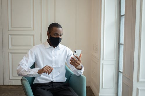 Black male executive in white shirt and fabric mask sitting in armchair while talking on cellphone during video chat indoors