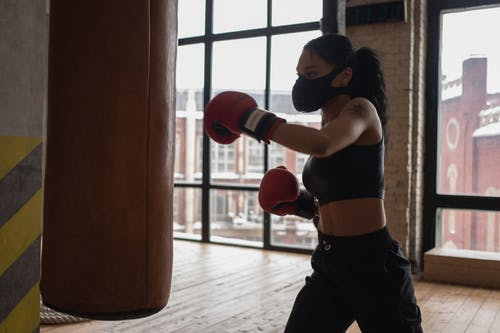 Determined African American female fighter in cloth face mask and gloves during workout against boxing bag in gym