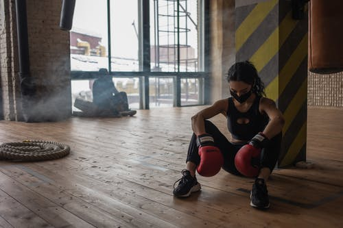 Tired black boxer resting on floor in gym