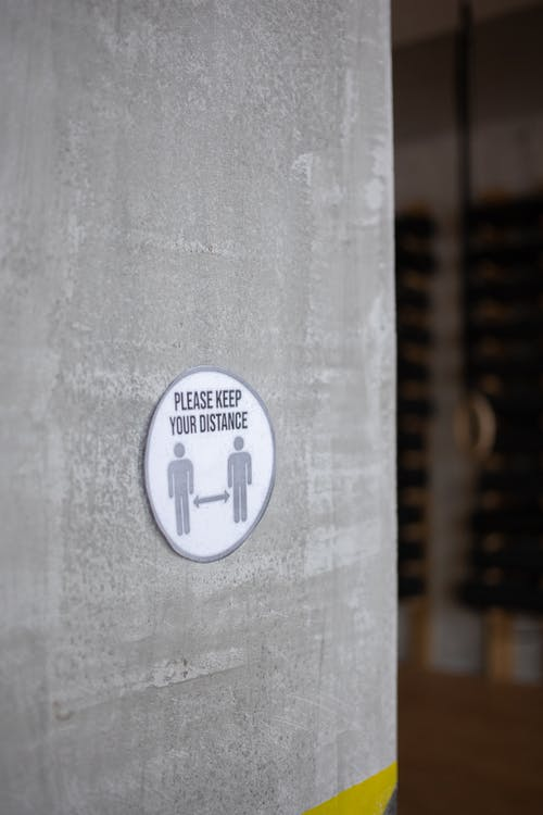 Round sign with Please Keep Your Distance inscription over figures and arrows on cement wall during COVID19 pandemic in gym