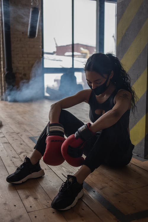 Exhausted black sportswoman in boxing gloves and cloth face mask having break from training on floor in gymnasium