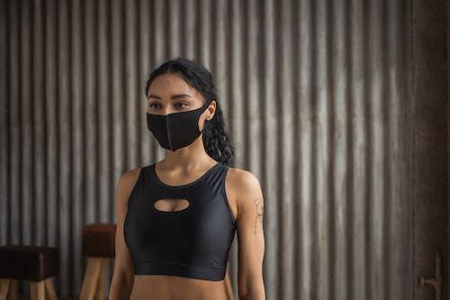 Black sportswoman in fabric mask in gym