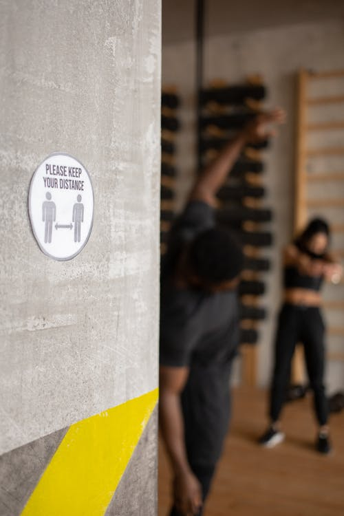Please Keep Your Distance inscription on sign with arrows and figures against anonymous black sportspeople working out in gym