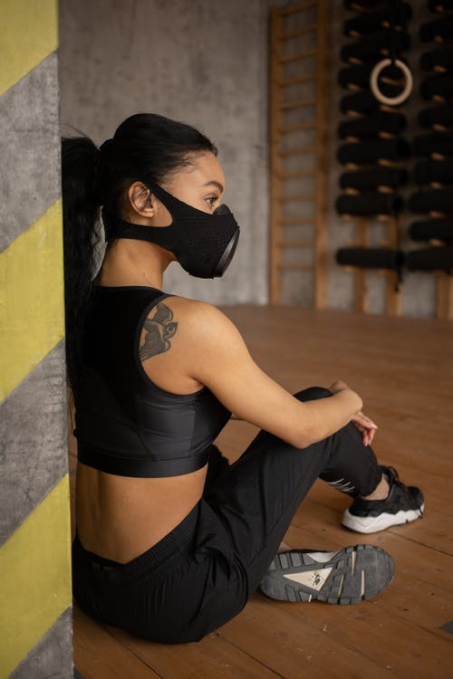 Back view of African American female athlete in sportswear and protective respirator sitting on floor in fitness studio