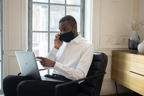 Black businessman in mask using laptop while talking on smartphone
