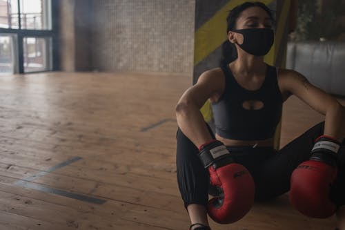 African American female boxer in protective mask resting on floor after training in fitness center