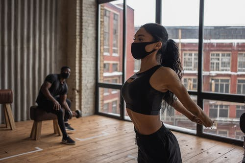 Fit African American sportswoman in mask stretching arms while training in gym during coronavirus pandemic with man lifting dumbbell