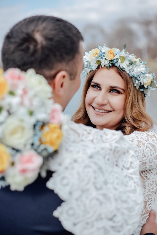Loving bride in white dress and wreath smiling happily while embracing groom at wedding ceremony