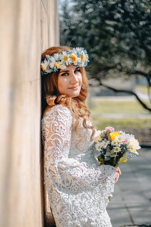 Charming woman in bridal dress with bouquet of flowers
