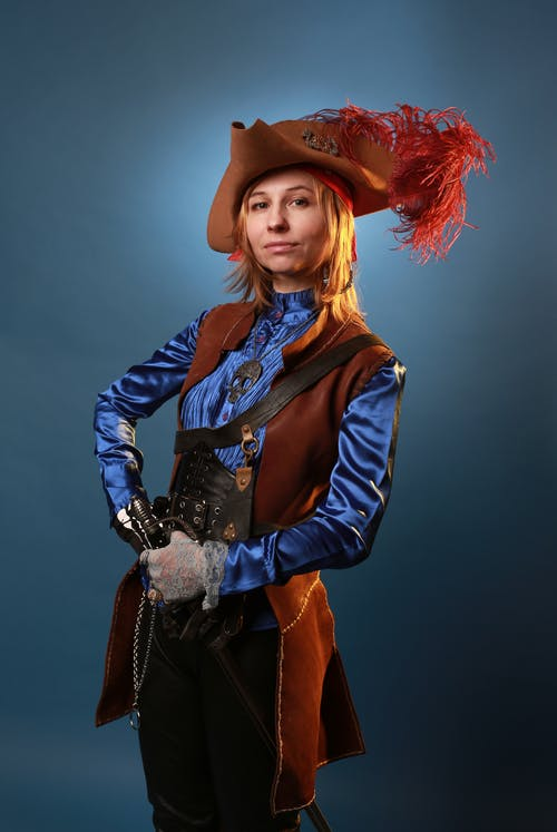 Confident model in pirate costume on gray background