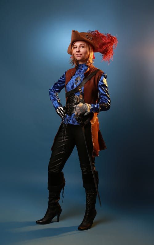 Model in pirate costume on gray background