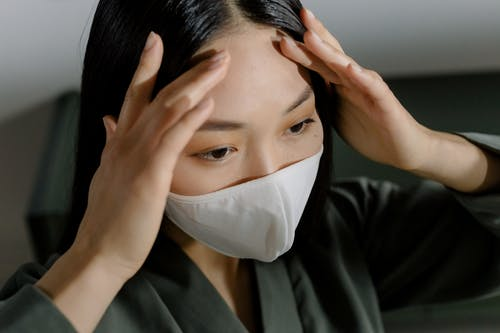 Woman in Black Suit Covering Face With White Face Mask