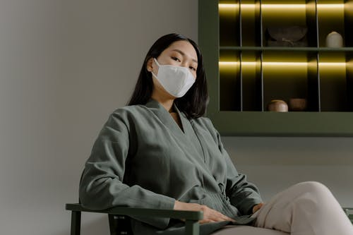 Woman in Gray Long Sleeve Shirt Wearing White Face Mask