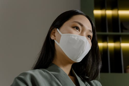 Young Asian female with long dark hair in medical mask and gray jacket looking away against white wall