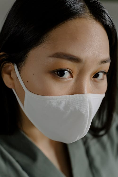 Beautiful young Asian female with dark hair and makeup in white protective mask looking at camera