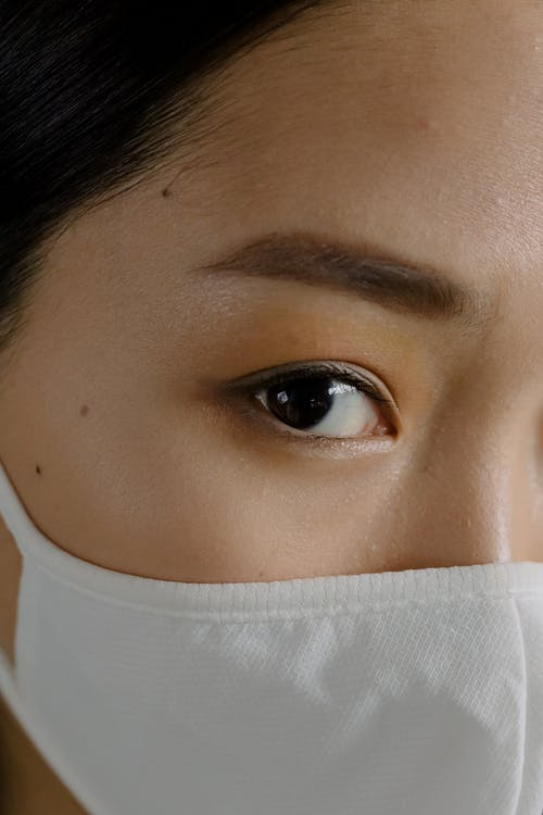 Closeup crop young Asian female with nude makeup in white protective mask looking at camera