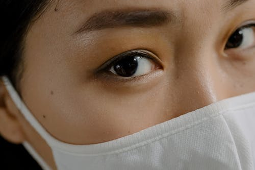 Crop woman with brown eyes in mask