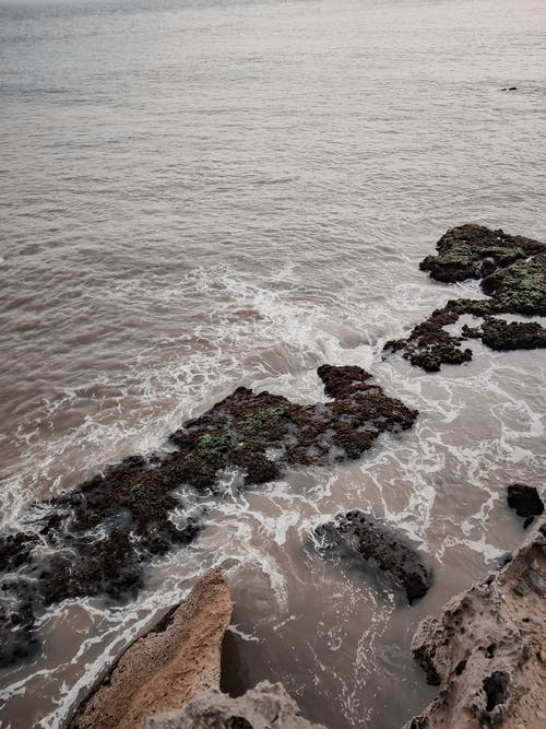 From above of rippling foamy sea crashing on rough stony shore with rocky formations in nature in coastal terrain on waterfront