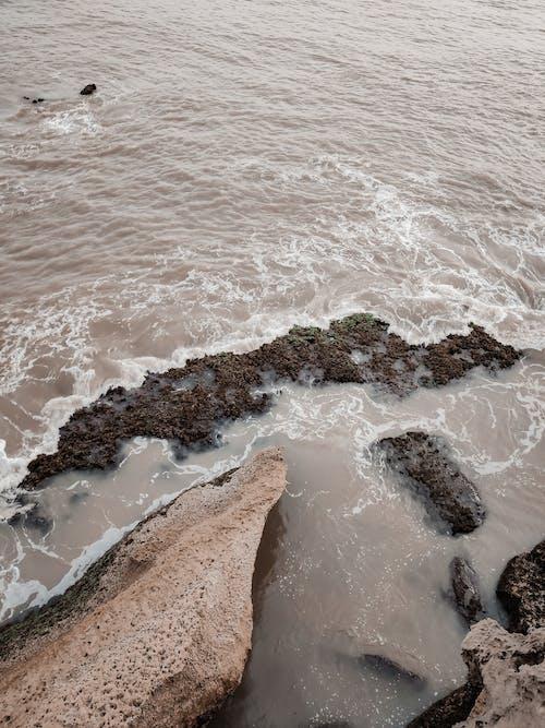 Rippling sea splashing near rocky shore