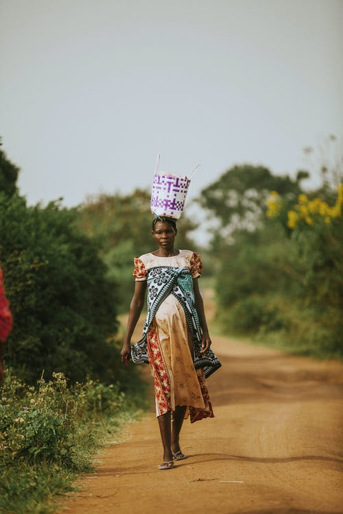 Woman Carrying a Bag on Her Head While Walking
