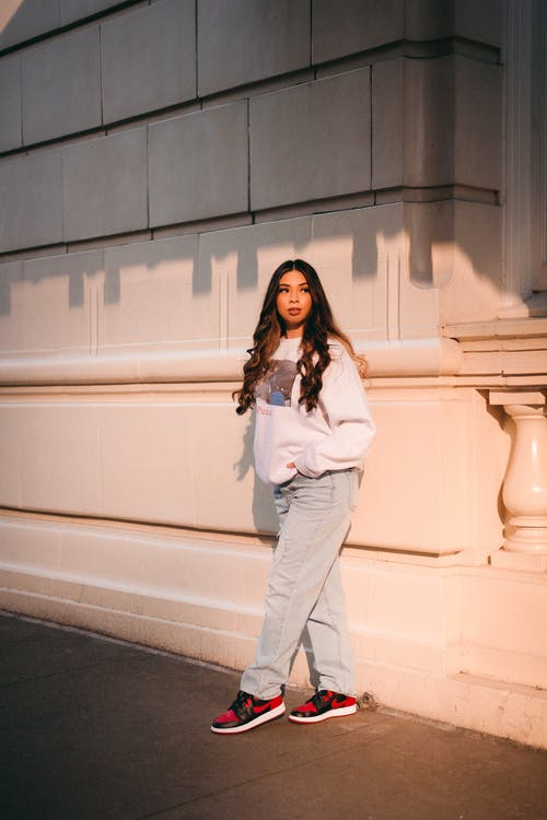 Woman in White Long Sleeve Shirt and Gray Pants Standing Beside White Concrete Wall