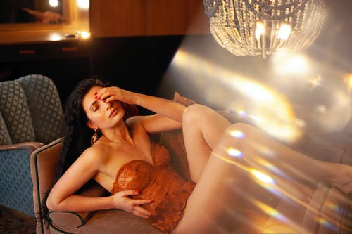 Sexual female in red underwear lying on couch with closed eyes and hand on head in room with glowing lights