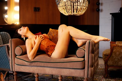 Provocative woman in lingerie lying on couch