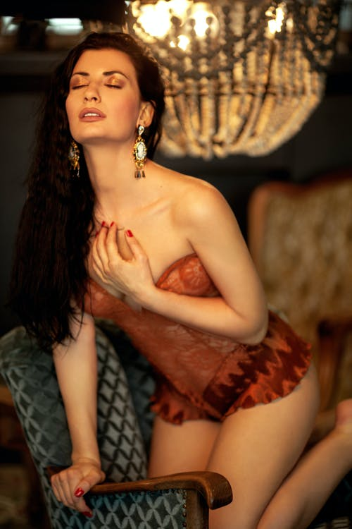 Sensual female with makeup and black hair wearing red underwear sitting in armchair with hand on chest in room with chandelier