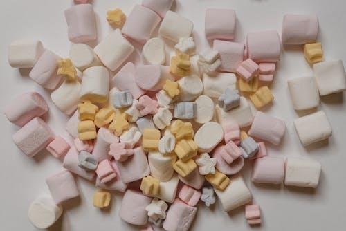 Many tasty marshmallows heaped on white table