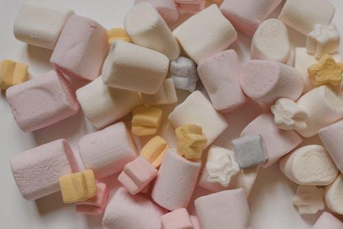 Delicious marshmallows heaped on white table