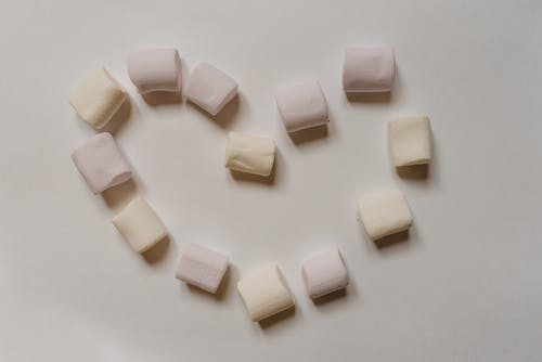 Sweet marshmallows arranged on table in shape of heart