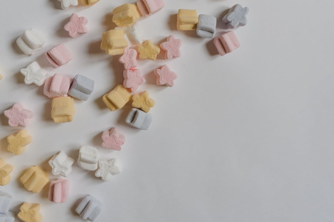 Top view arrangement of multicolored yummy marshmallows in shape of stars scattered in corner of white paper