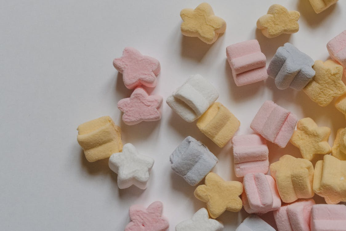 Top view yummy multicolored marshmallows scattered in shape of stars scattered on corner of white table
