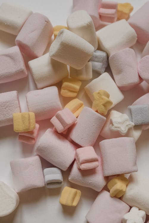 Top view yummy delicious marshmallows of different shapes and colors heaped on white table