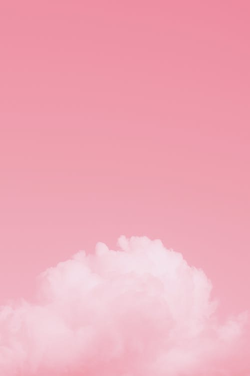 Bright pink colorful sky with white soft fluffy cumulus clouds floating in daylight