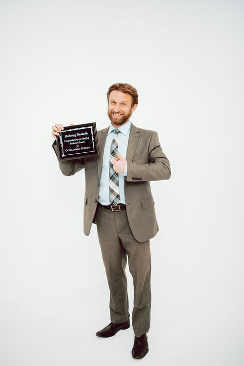 Man in Gray Suit Holding Black and White Card