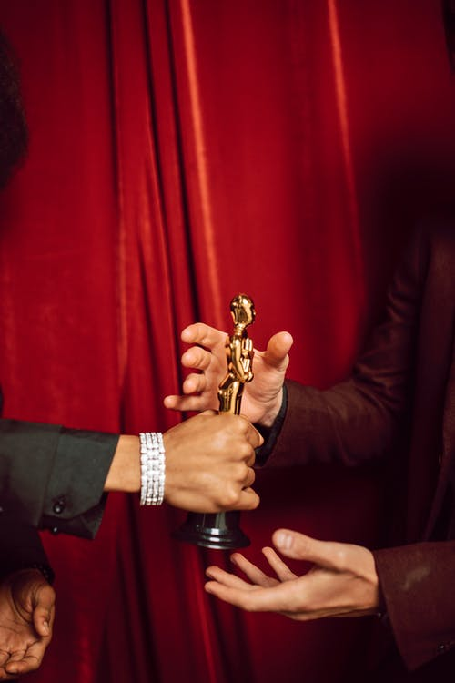 Man in Black Suit Holding Brass Trophy