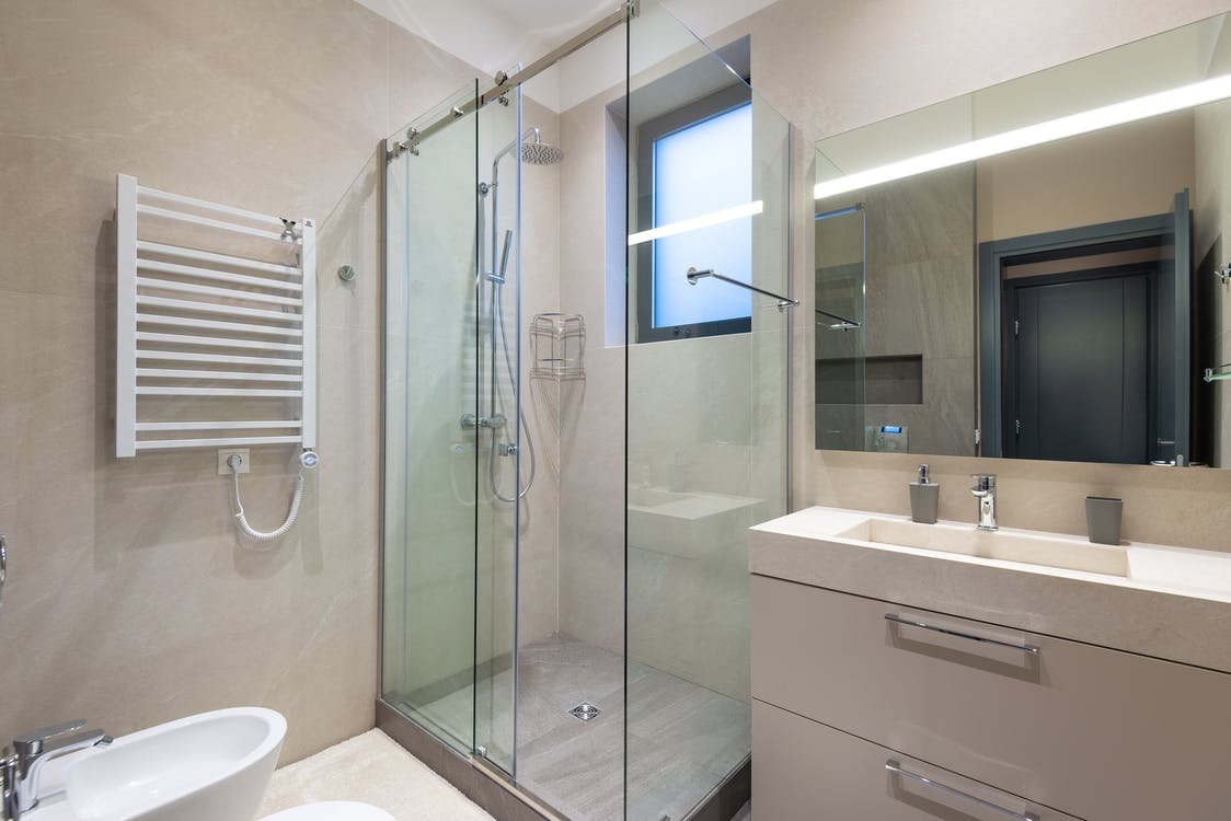 Shower cabin with glass walls near mirror hanging on wall above sink in modern minimalist styled bathroom