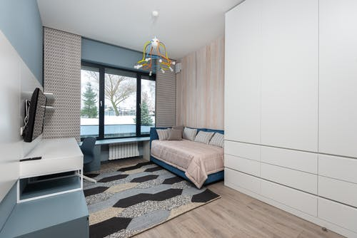 Bedroom with sofa and workspace in modern apartment
