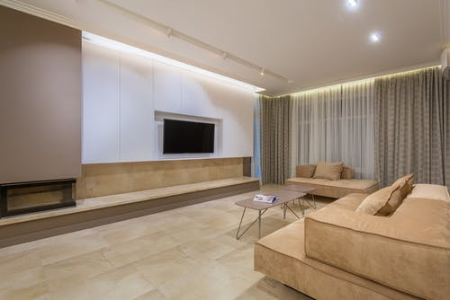 Minimalist design of spacious living room with big comfortable beige sofas placed in front of TV in modern apartment with illuminated stretch ceiling