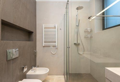 Ceramic bidet and shower cabin in contemporary bathroom