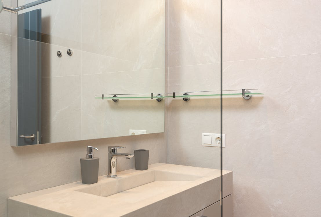 Through glass of shower cabin on sink and mirror in modern bathroom with tiled walls