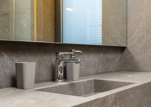 Details of contemporary bathroom with marble tiles and mirror