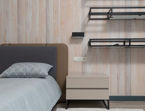 Wooden nightstand and empty shelves near comfortable bed with cushions in modern apartment