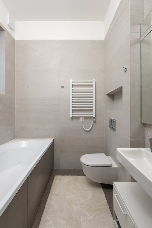 Ceramic bathtub with toilet bowl and sink in modern bathroom with beige tiled walls