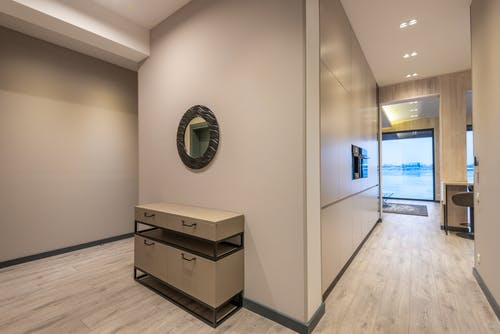 Round mirror and cabinet in spacious hallway of modern house with wooden parquet floor and panoramic windows