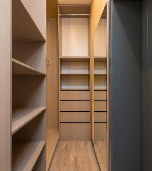 Minimalist styled empty built in closet with racks and shelves