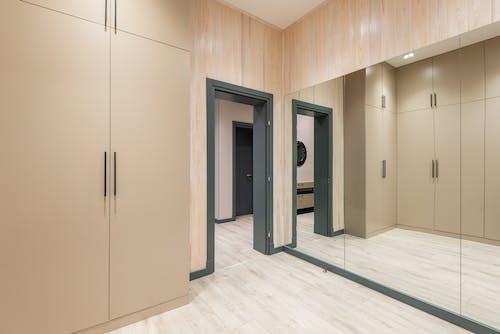 Big mirror on wall reflecting beige wardrobes in spacious corridor of modern apartment