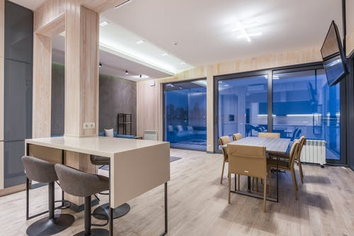 Dining tables with comfortable chairs in spacious apartment with wooden floor and walls and blue glass terrace doors