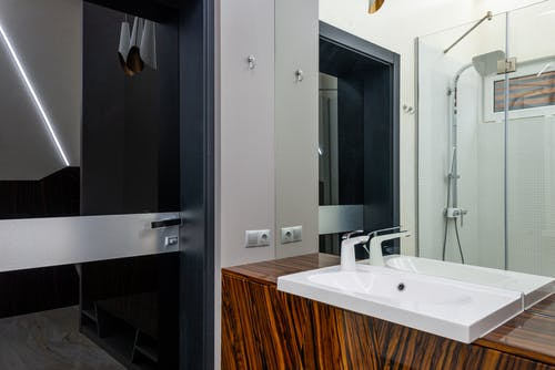 White ceramic sink with chrome faucet on wooden cabinet and shower cabin with glass walls in modern bathroom
